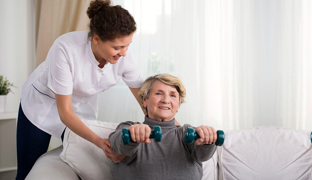 caregiver assisting senior woman physical therapy