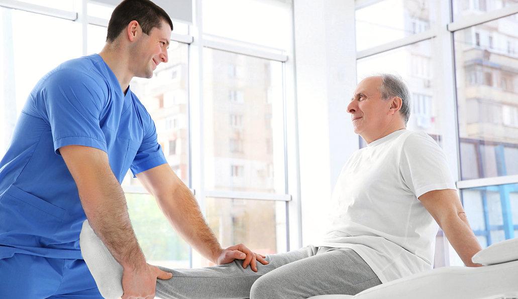 caregiver assisting senior man to his leg